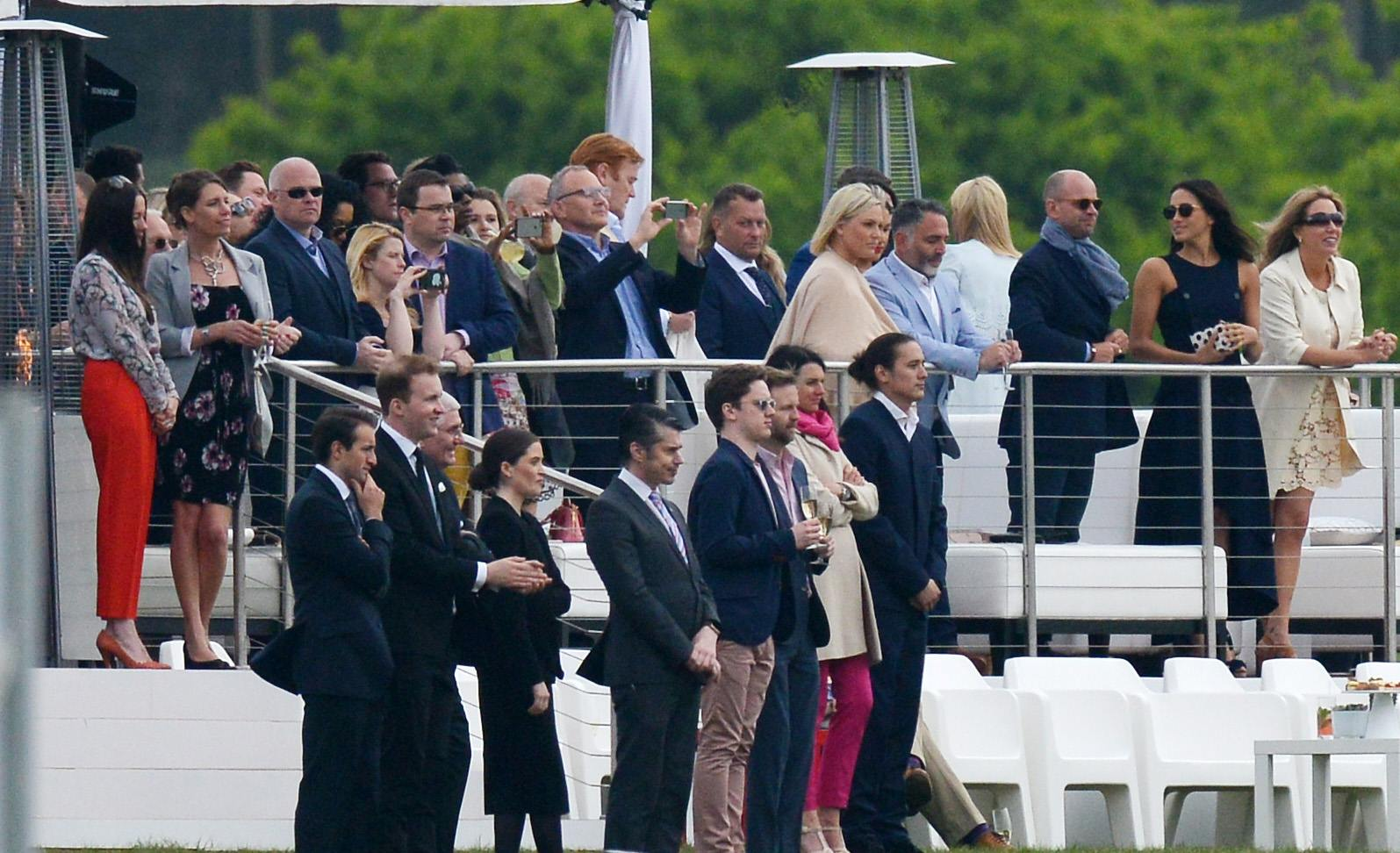 Meghan Markle watches Prince Harry play polo with with Prince Harry's mentor Mark Dyer and wife (right) at the Audi Polo Challenge. Mark at one point went and got her jacket.